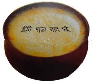 It says in Bengali: reddish white yogurt baked with sugar.